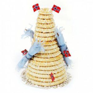 Kransekake med atten ringer pyntet med norske flagg og blå smellbonboner